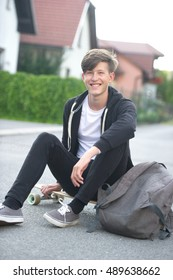 Smiling teenager sitting on his longboard while smiling to the camere on a suburban street.