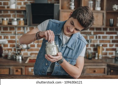 smiling teenager taking dollar banknotes from saving glass jar for money
