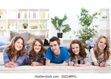 Smiling teenagers friends lying on floor in row