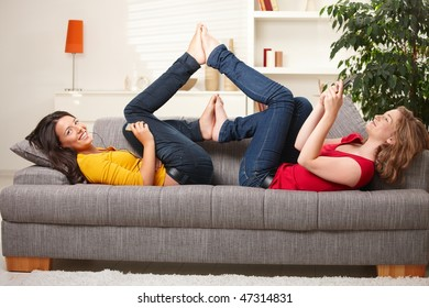 Smiling teens lying on couch with feet put together playing with mobile phone listening to music.