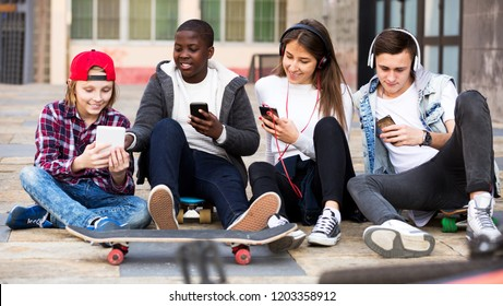 Smiling teens playing on smarthphones and listening to music