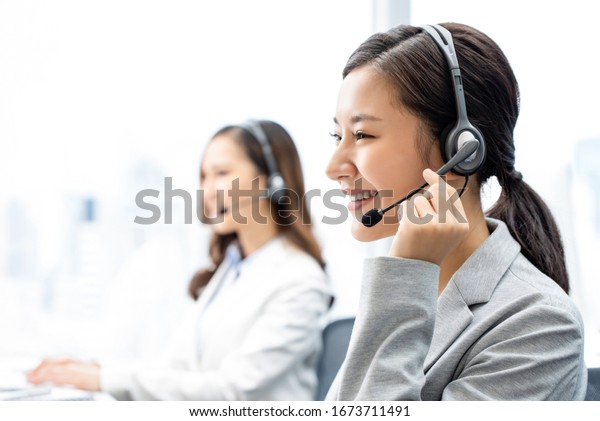 Smiling telemarketing Asian woman working in call center office
