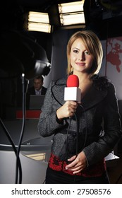 smiling television news reporter in live transmission with braking news in studio
