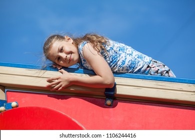 Smiling ten years old girl on red construction of children playground against blue sky