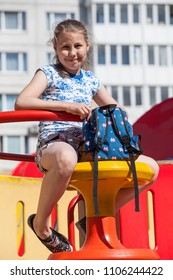 Smiling ten years old girl sitting with backpack in hands on children playground