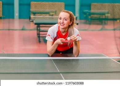 the smiling tennis player standing at the table for table tennis and keep the ball on the racket