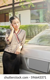 Smiling Thai woman in the local Asian fashion style portrait with cars.