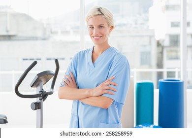 Smiling therapist with arms crossed in fitness studio