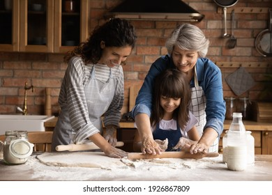 Smiling three generations of Hispanic women have fun baking together with dough at home kitchen. Happy little Latino girl child with young mom and senior grandmother cook pastries or cookies.