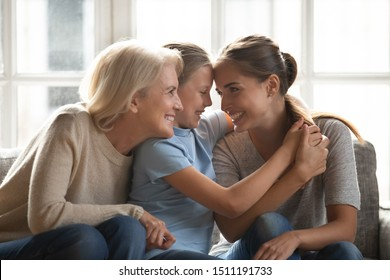 Smiling three generations of women sit on couch at home hugging cuddling having fun together, happy mother, daughter and grandmother embrace enjoy family weekend show love and support