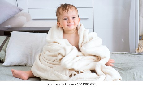 Smiling toddler boy covered in white towel after bathing