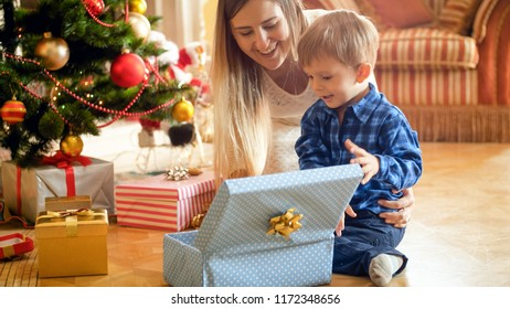 Smiling toddler boy looking inside of Christmas gift box