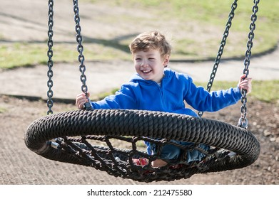 Smiling Toddler Boy on a Swing in the Park
