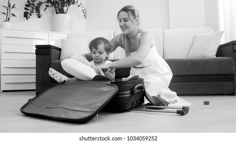 Smiling toddler boy sitting in suitcase while mother packing things for traveling