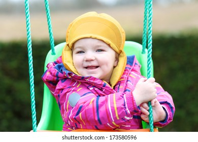 Smiling toddler girl in multicolor jacket and orange hat rocking outdoors on the swing