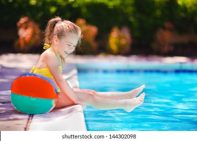 Smiling toddler girl playing with toy in outdoor swimming pool