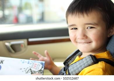 Smiling toddler inside a car.
