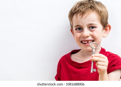 smiling toothless 7-year old boy finding the key for fun tooth fairy, growing up idea or solution to child healthcare, copy space white background