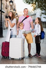 Smiling tourist family with children using map and making amateur photo of sights in Europe city