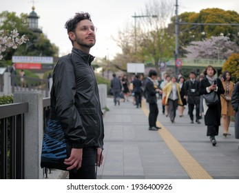 Smiling tourist looks around on the streets of Tokyo. Pleasure of traveling in the period of cherry blossoms. Happy tourists and Japanese people.