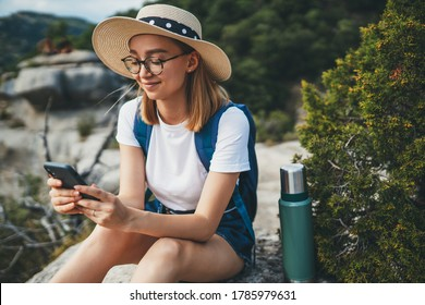 smiling tourist woman in hipster glasses and hat chatting on cellphone and relaxing while walking on tops of mountains, blonde young girl traveler hiking summer outside enjoys leisure on nature