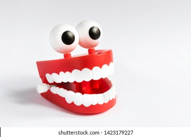 A smiling toy denture, chattering teeth with a spring that opens and closes by vibrating, with white teeth, ball eyes and gums, isolated on a uniform white background