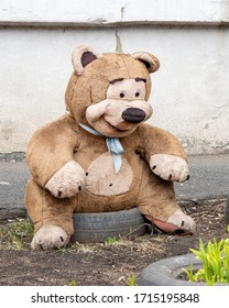 A smiling toy of a quiver dirty dirty big teddy bear, lost and forgotten. Bear alone on the ground. Love expectation