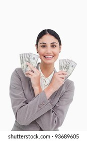 Smiling tradeswoman with money in her hands against a white background