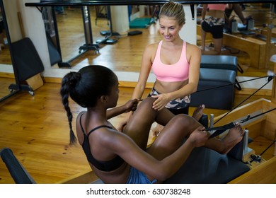Smiling trainer assisting woman with pilates on reformer in fitness studio