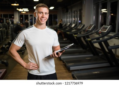 Smiling trainer in the gym with a clipboard in his hands.