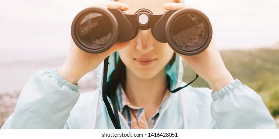 Smiling traveler explorer young woman looking through binoculars in summer mountains outdoor, front view, close-up. Image with sunlight effect.
