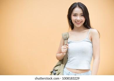 Smiling traveler woman on orange background