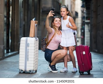 Smiling travelers woman and girl photographed on phone in old European city