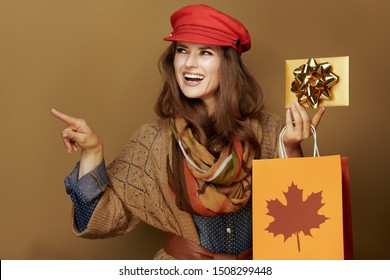 smiling trendy 40 year old woman in red cap, scarf, jeans shirt and cardigan with autumn shopping bag and golden gift card pointing at something on beige background.