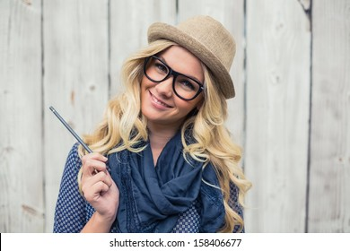 Smiling trendy blonde holding pencil on wooden background