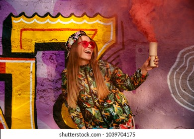 Smiling trendy girl in colorful stylish clothes with smoke flare, having fun time, standing near the wall with graffiti. Outdoors.