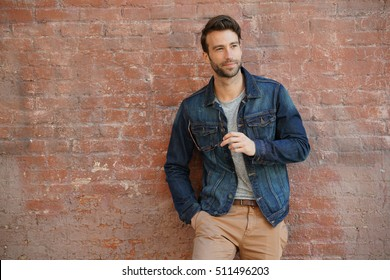 Smiling trendy guy with blue jeans jacket and eyeglasses standing by brick wall