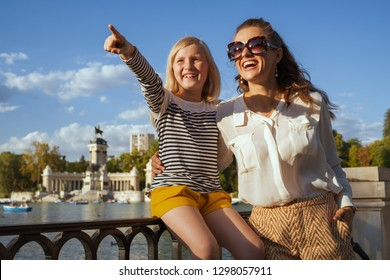 smiling trendy mother and child travellers at Parque del Buen Retiro in Madrid, Spain pointing at something. Madrid is the sunny capital of Spain. family trip to Madrid. having micro trip. blue sky.