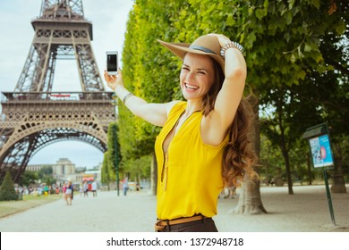 smiling trendy solo traveller woman in yellow blouse and hat taking photo with cellphone in the front of Eiffel tower in Paris, France.