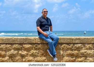 Smiling trendy tourist elderly man sitting by old brick historic stone. Portrait of handsome aged fashion senior wearing black t-shirt and jeans on blue sea and sky background. Vacation concept.