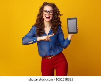 smiling trendy woman with long wavy brunette hair pointing at tablet PC blank screen isolated on yellow