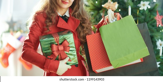 smiling trendy woman in red trench coat with shopping bags and Christmas present box near Christmas tree