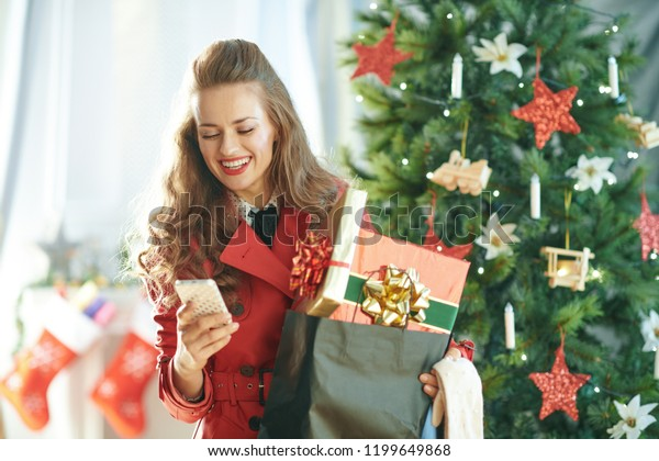 smiling trendy woman in red trench coat with shopping bag full of Christmas present boxes sending text message from phone near Christmas tree