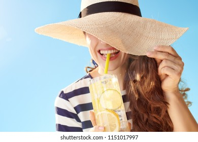 smiling trendy woman in straw hat against blue sky hiding behind straw hat and drinking refreshing cocktail