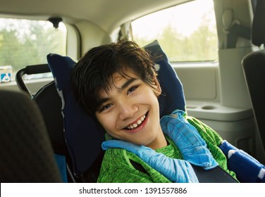 Smiling twelve year old biracial disabled boy in handicap vehicle sitting in wheelchair