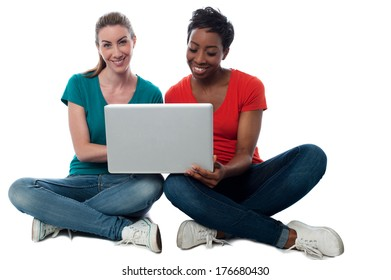 Smiling two friends watching videos on laptop