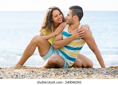 Smiling two having romantic date on sandy beach at sunny day