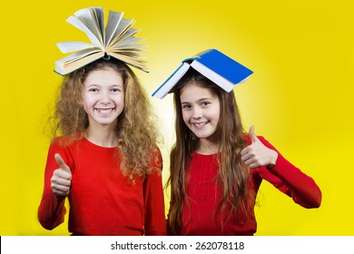 Smiling  Two sisters , little schoolgirl  with thumb up and books on their head, isolated over yellow background.
