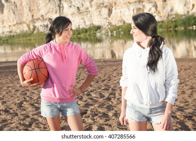 Smiling two women holding a basketball at the beach