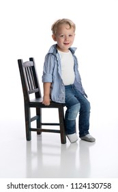 A smiling two year old boy sitting on a child's chair. Shot in the studio on a white, backdrop.